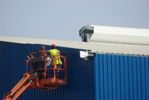 Trabajadores en plataforma elevadora revisando techo de nave industrial