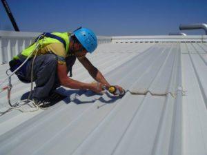 Trabajador aplicando material correctivo en techo de nave industrial