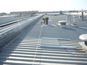 Trabajador reformando techo de nave industrial